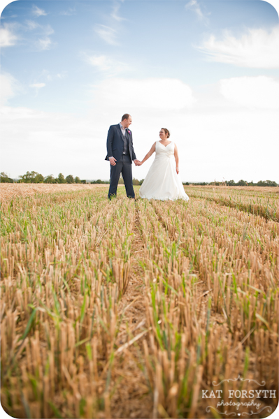 Couple in field blue skies wedding
