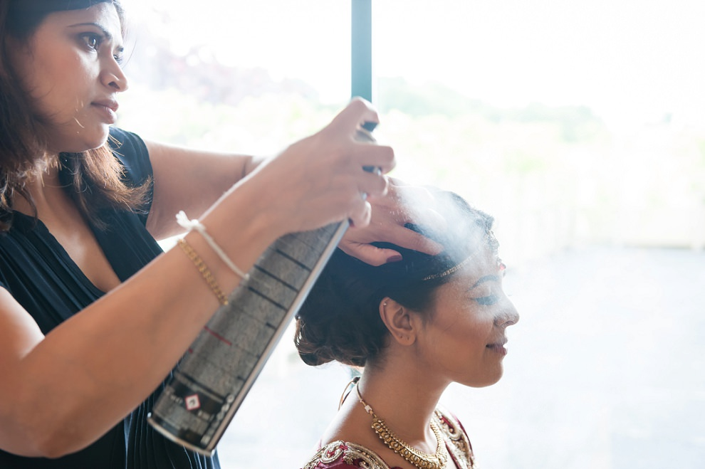 Hindu bride getting ready with hairspray