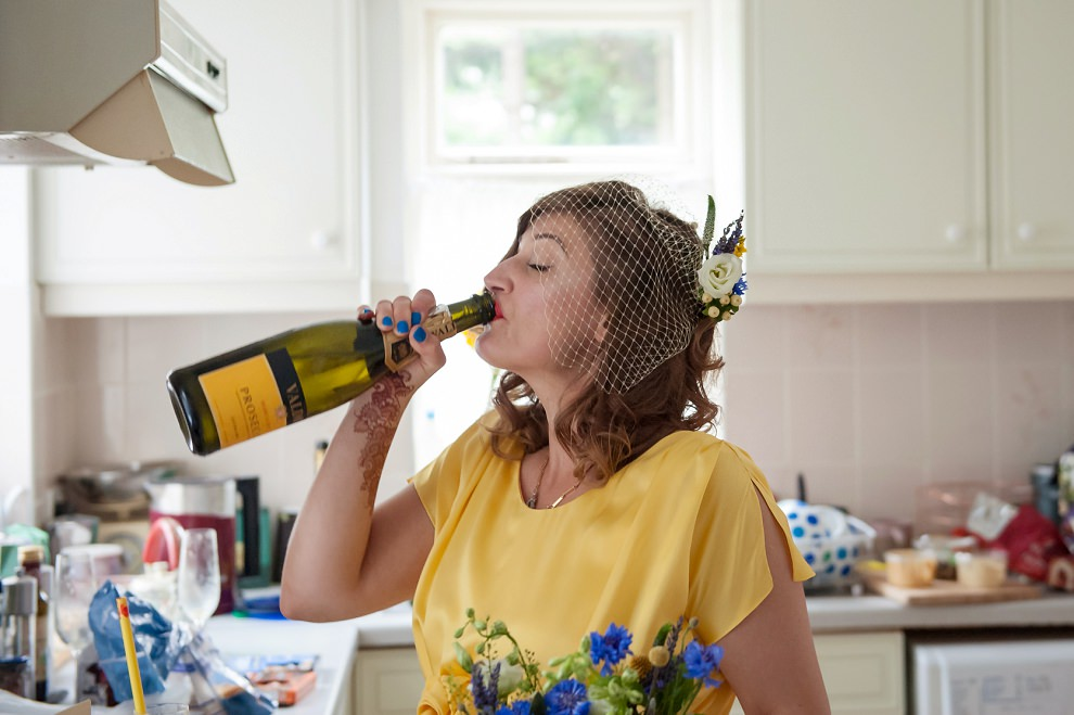 Funny bride drinking prosecco from bottle