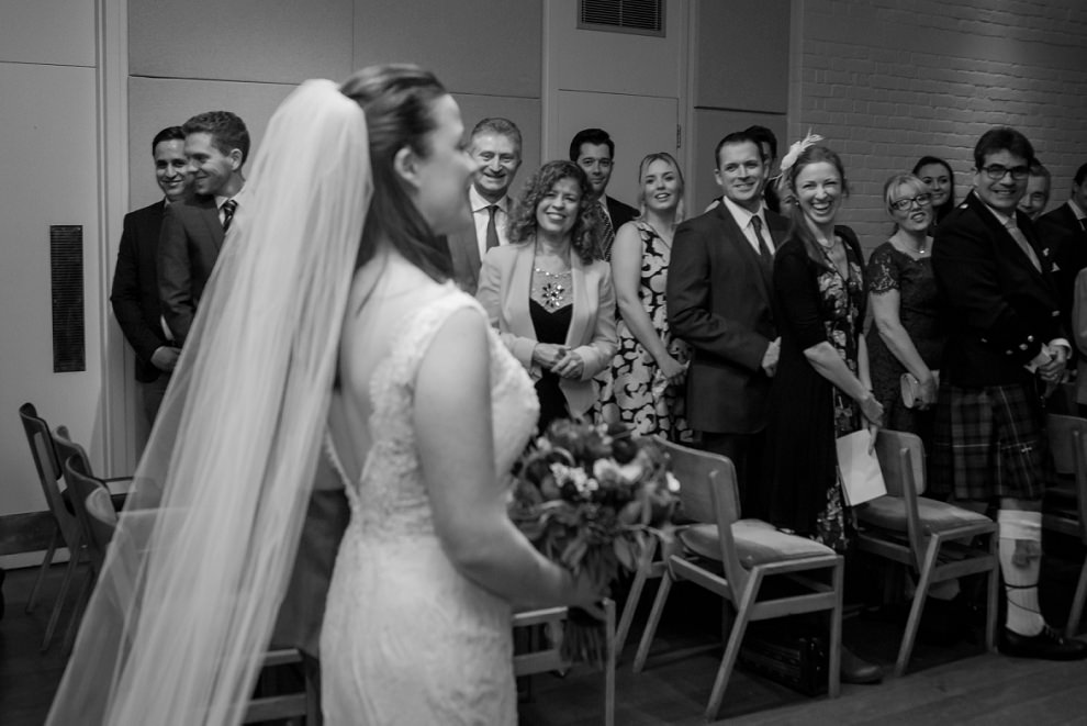 Wedding guests smiling as bride walks down the aisle