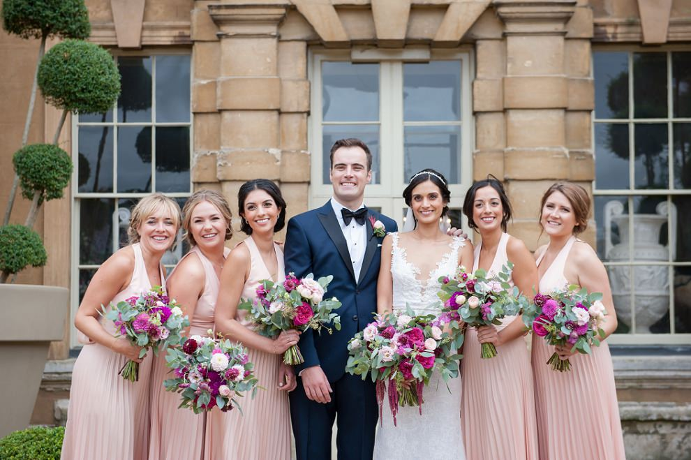 Bridesmaids and wedding couple outside Aynhoe Park