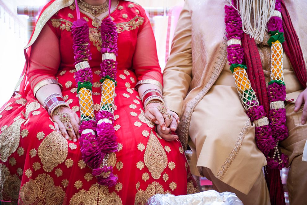 colourful outfits and garlands at a Hindu Wedding
