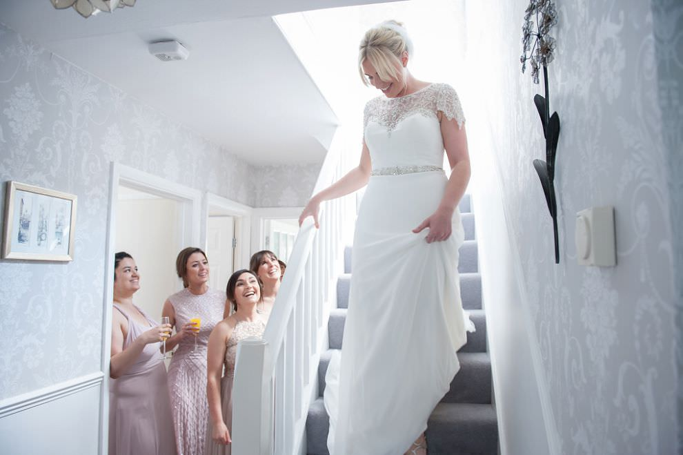 Bride coming downstairs watched by bridesmaids