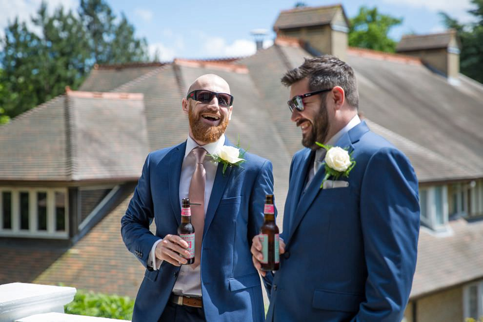 groom and best man laughing at Laura Ashley Hotel wedding