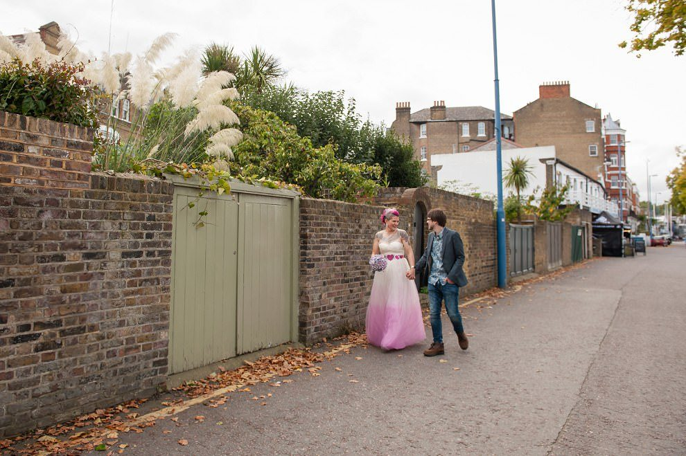 Wedding photographers London | Bride and Groom walking down street in Putney