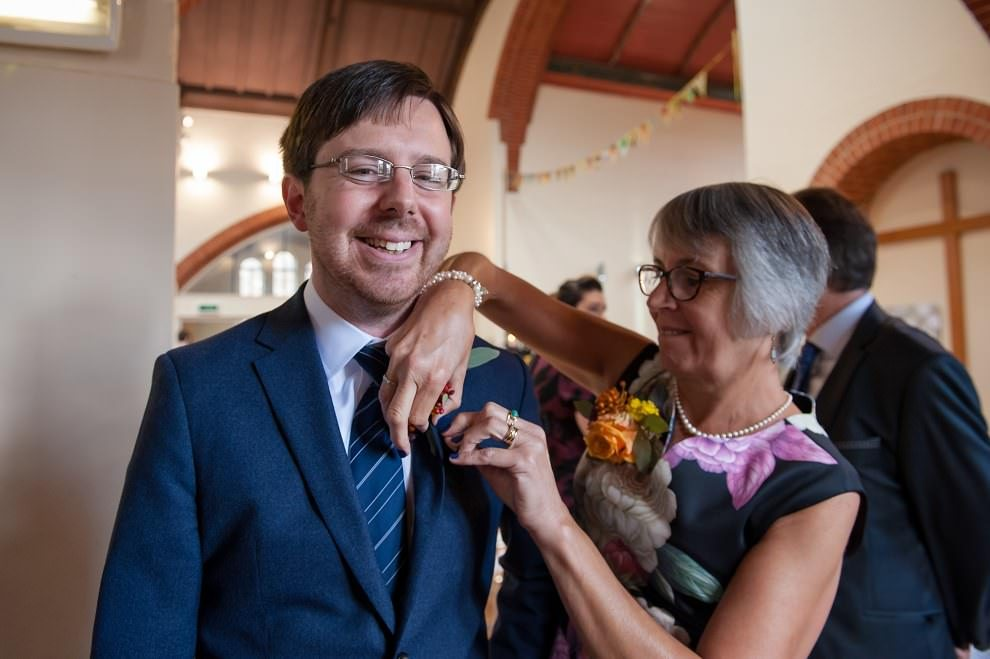 Wedding photographer London | mother of groom putting on buttonhole