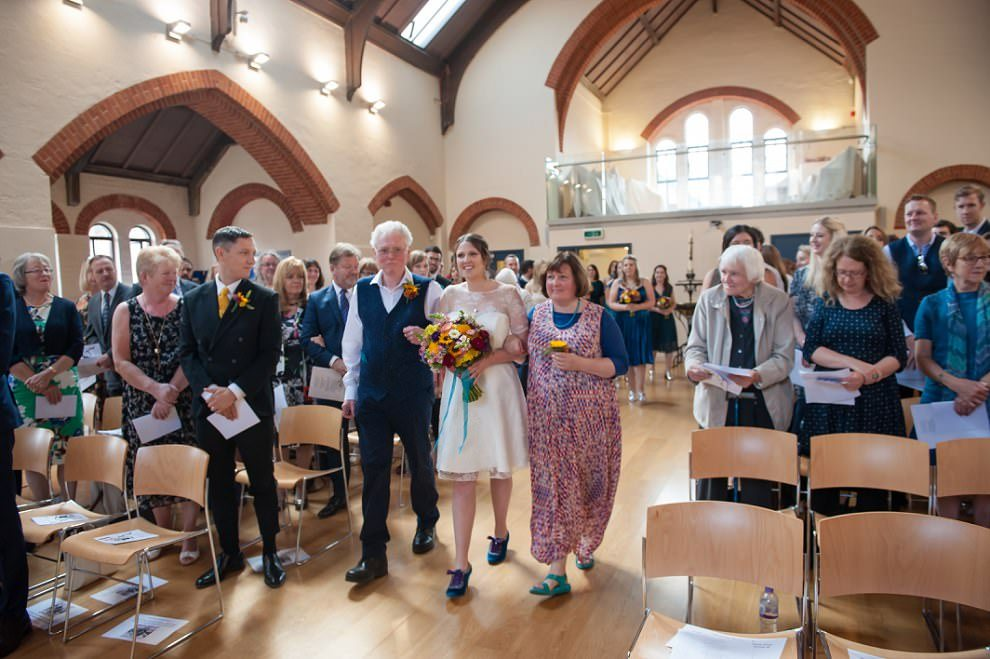 Alternative wedding Photographer London | Bride walks in with both parents