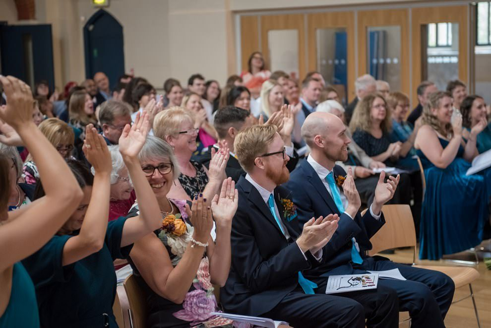Wedding photographer London | Guests clapping at first kiss in ceremony
