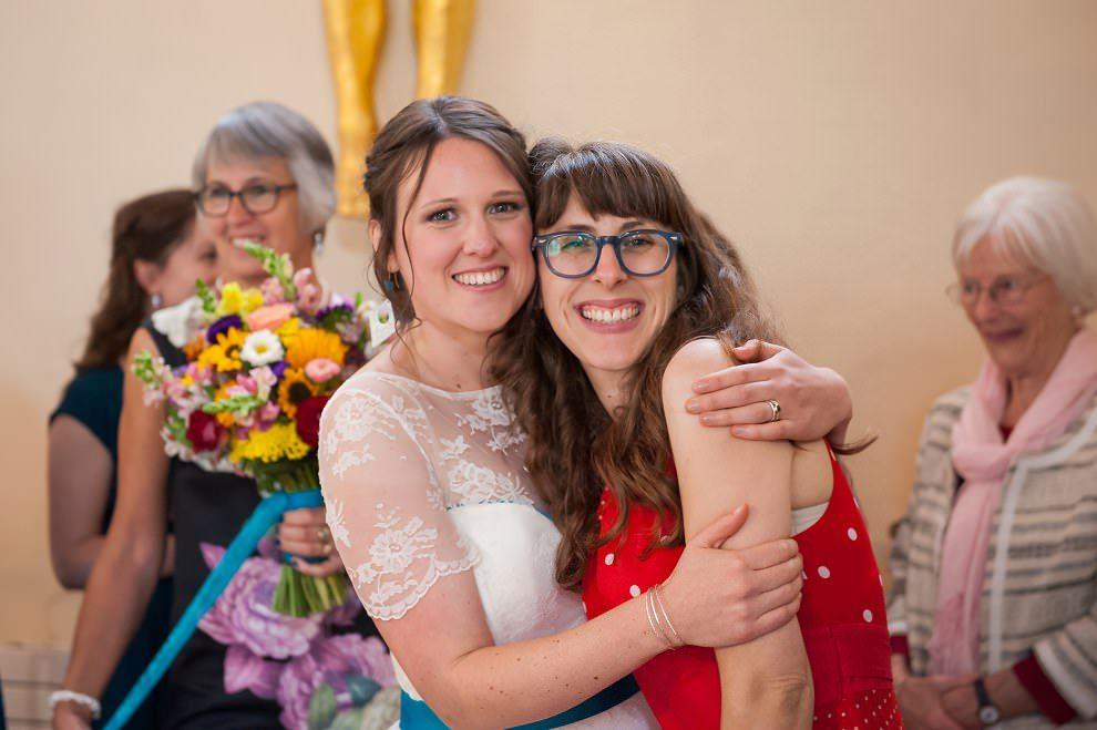 Bride hugging friend | Top UK wedding photographers