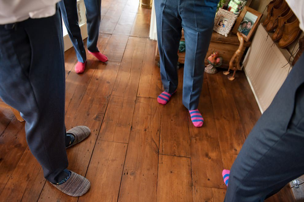Quirky wedding photography | groom getting ready with pink socks