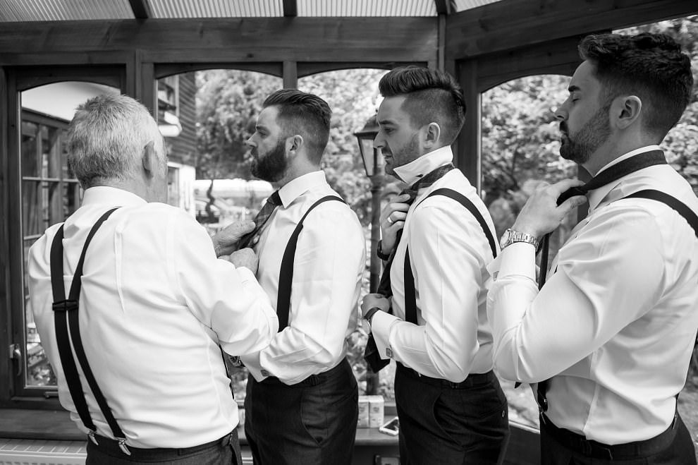 Documentary wedding photographer | Groomsmen putting on ties
