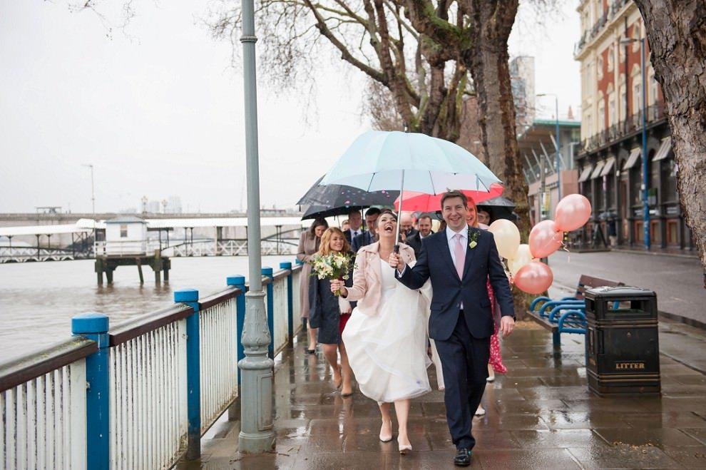Bride and groom rainy wedding walking in the rain